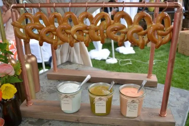 pretzel station with hanging pretzels and dipping sauces