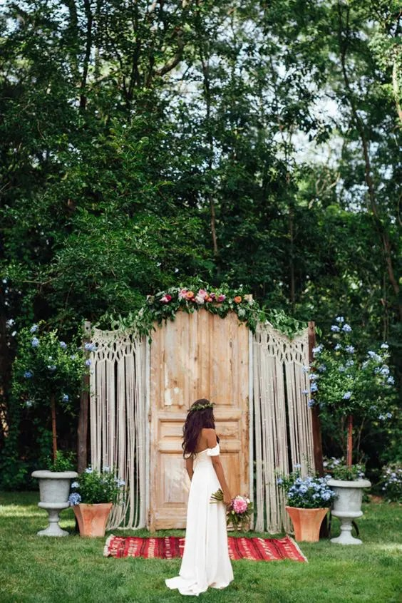 a door backdrop with macrame decor, flowers and a bold rug