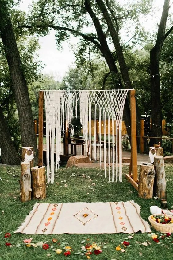 boho wedding arch with a macrame hanging, an embroidered rug and wooden logs