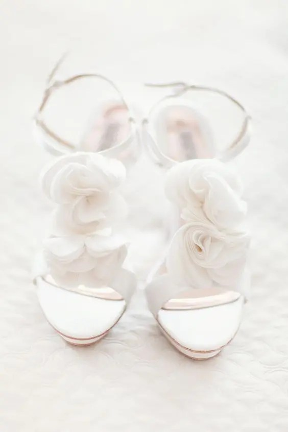 all-white heeled sandals with akle straps and fabric flowers