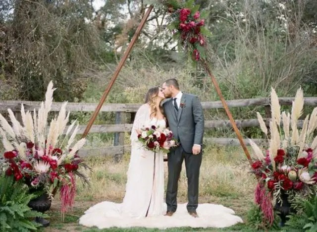 triangle wedding arch with bold flowers and pampas grass on the sides