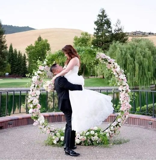 a blush flower and greenery wreath and a lake behind for a gorgeous backdrop