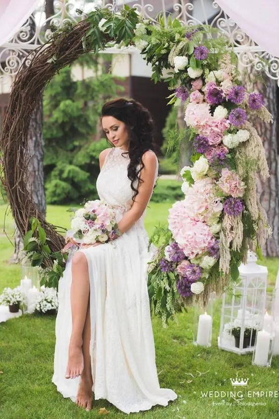 oversized wreath with lilac-colored and blush flowers on one side used as a swing