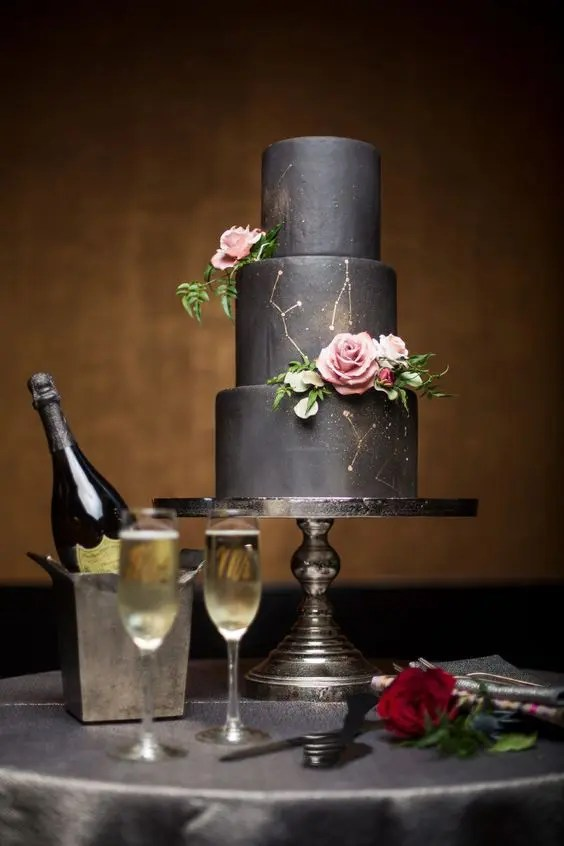 Picture Of black wedding cake with gold constellation and fresh roses