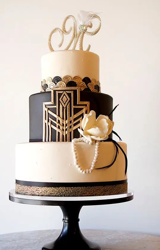 Picture Of a black  white and gold wedding cake with geo decor     Picture Of a black  white and gold wedding cake with geo decor  buttons   edible pearls  a sugar flower and a rhinestone monogram