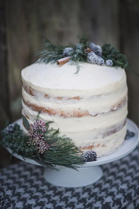 a beautiful and simple semi naked wedding cake topped with sugared blueberries, cinnamon sticks and evergreens