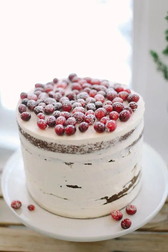 a semi naked wedding cake topped with sugared cranberries is ideal for a cozy winter celebration