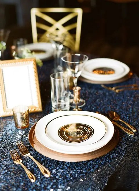 a navy sequin tablecloth, gold cutlery, chargers and candle holders for an elegant setting