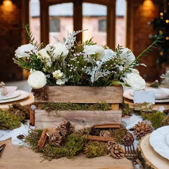 a rustic crate with greenery and flowers placed on moss with pinecones and cinnamon sticks for a great aroma