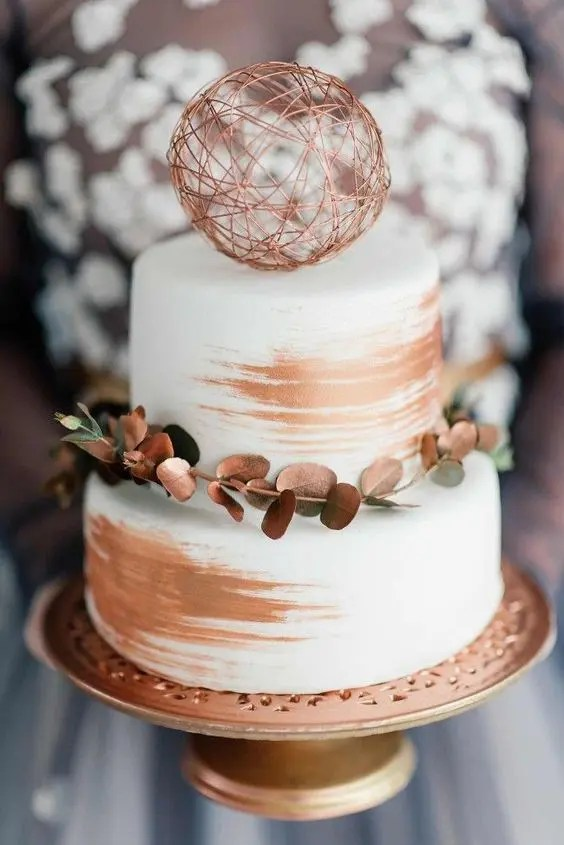 a white wedding cake decorated with copper, with a coppered greenery branch and a copper yarn ball on top