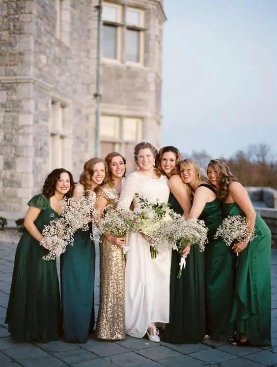 bridesmaids wearing emerald dresses and the maid of honor in a gold sequin gown
