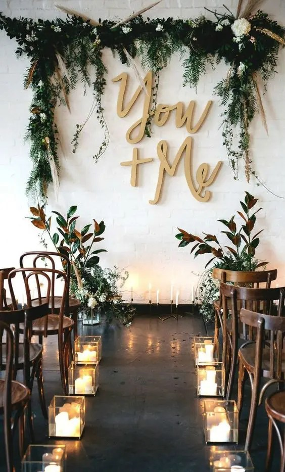 attach calligraphy letters, greenery and blooms right to the white wall to make a cool backdrop
