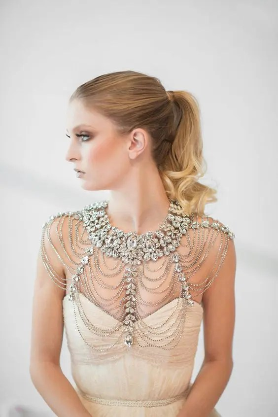 a statement bridal shoulder jewelry piece with lots of rows of beads and large rhinestones for a parkly bridal look