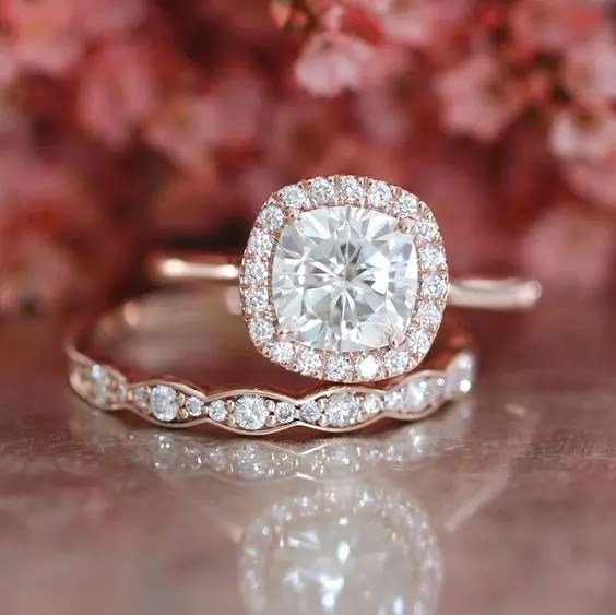 a rose gold engagement ring with a cushion diamond and a halo plus a matching wedding band with diamonds
