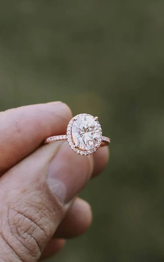 a rose gold engagement ring with an oval-shaped diamond and a halo around
