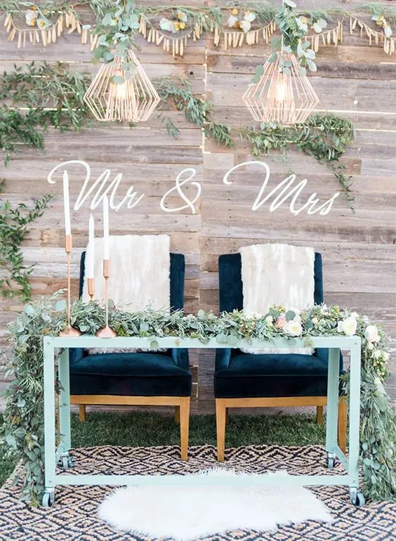 a reclaimed wood backdrop with garlands, greenery and two cool lamps for a boho wedding
