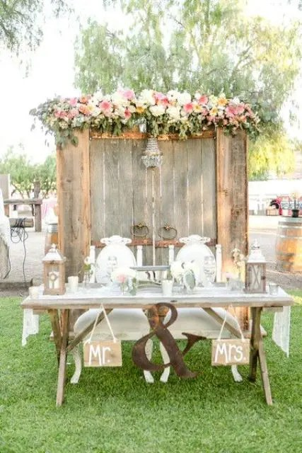 an old wooden door backdrop with a glam chandelier and lush blooms and foliage on top