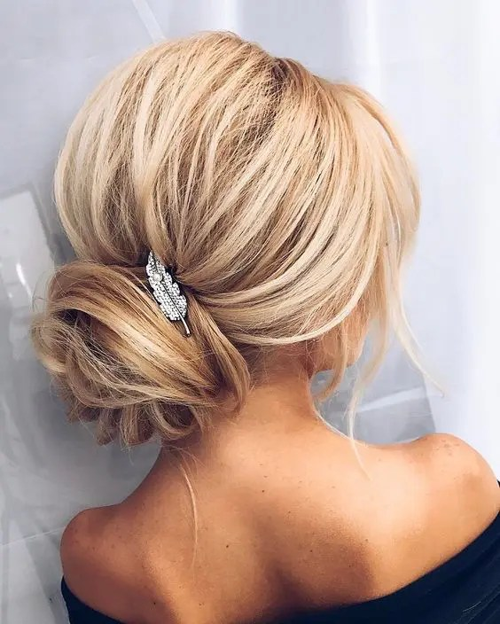 Picture Of a voluminous updo  with a wrapped low bun and a