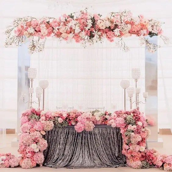 an airy fabric backdrop completed with lush florals that match the table runner