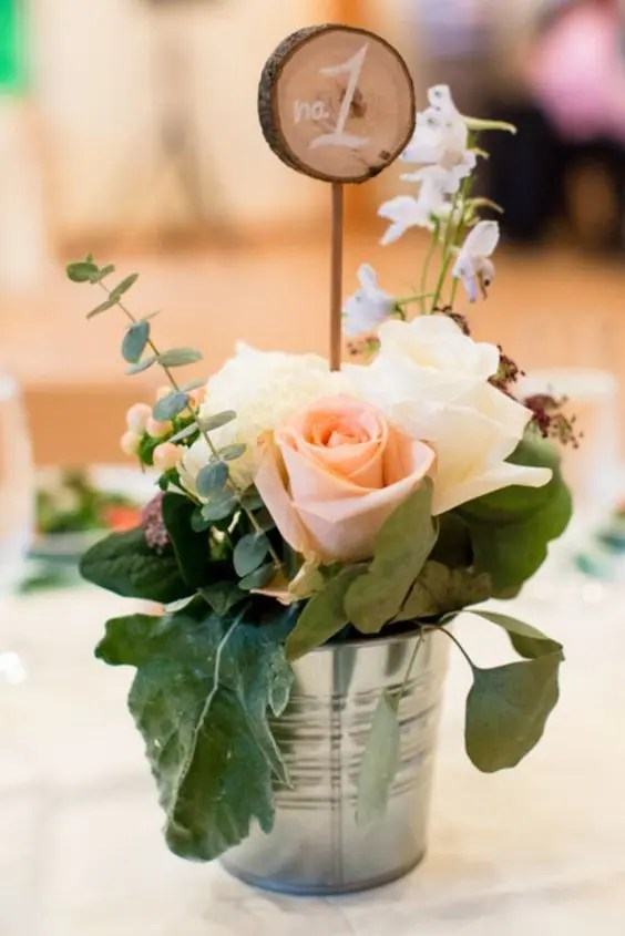 a bucket with greenery, neutral blooms and a wood slice number