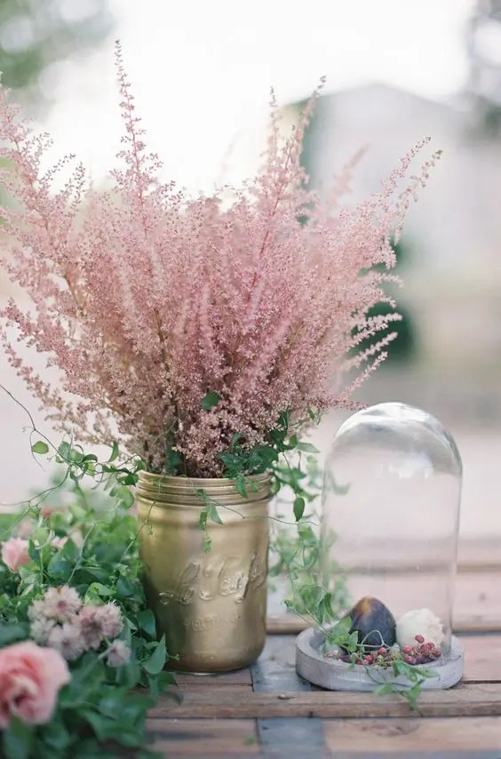 a gold mason jar with greenery and pink blooming branches