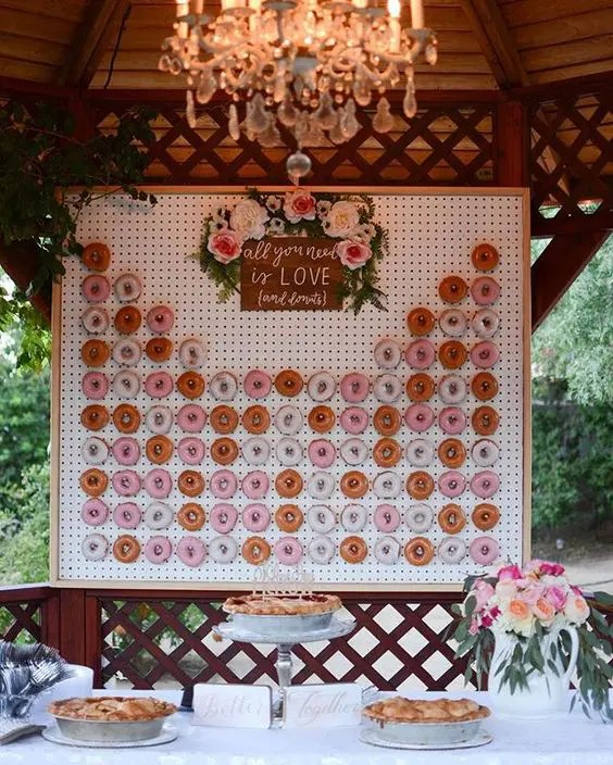 a framed pegboard donut wall topped with fresh blooms and a sign