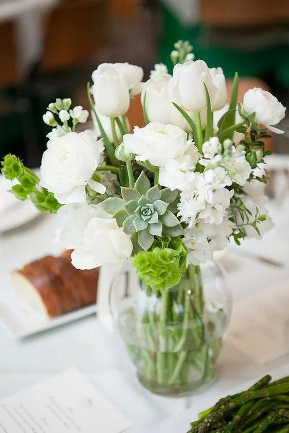 a sheer vase with white blooms, succulents and greenery