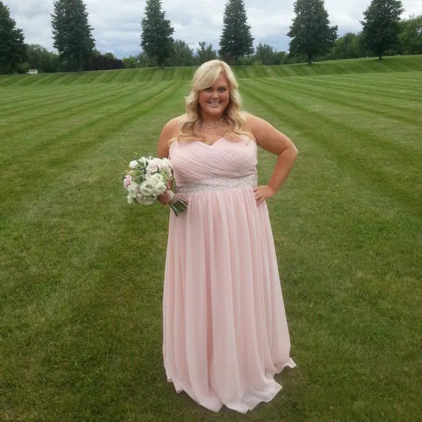 a light pink strapless maxi gown with a glitter sash and a statement necklace