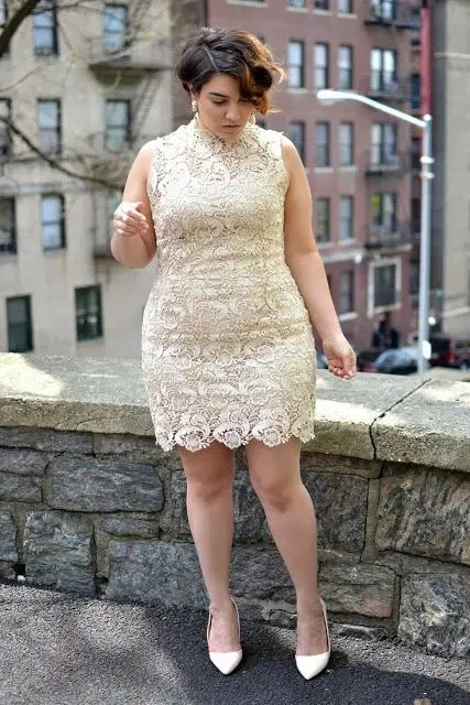a creamy lace over the knee dress with an illusion neckline and no sleeves