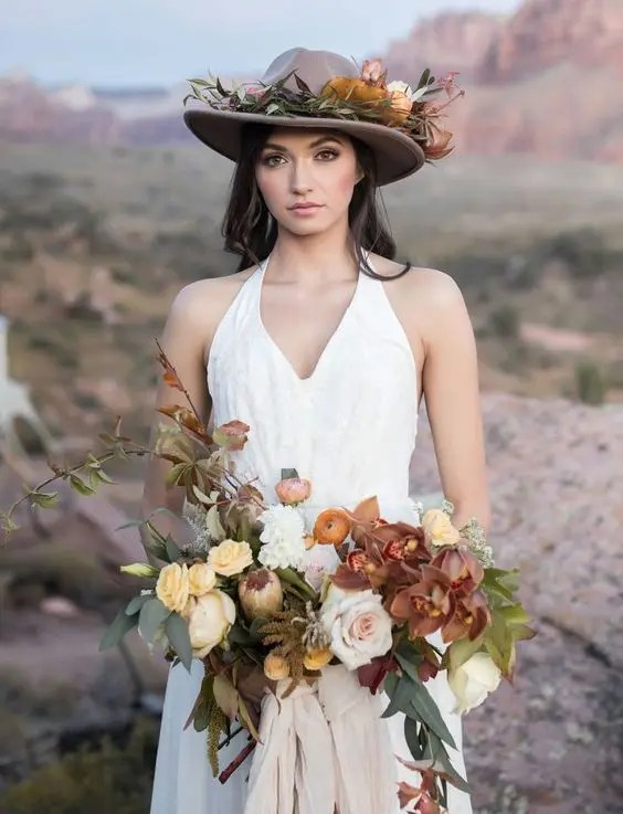 a brown hat decorated with flowers and greenery that match the bridal bouquet