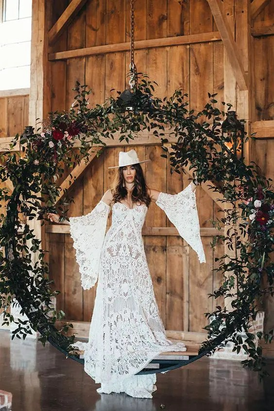 a boho bride wearing a boho lace wedding dress with bell sleeves and a white hat