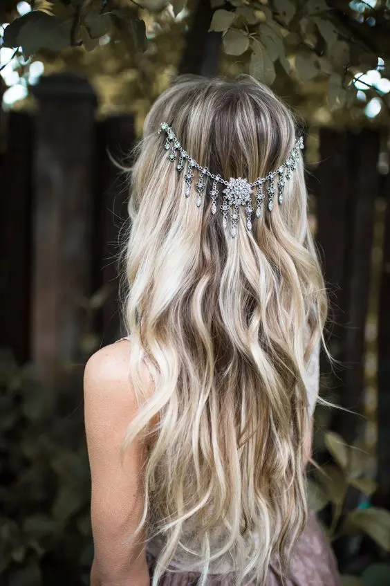 a boho chic wavy wedding hairstyle with silver jewel draped headpiece to highlight it
