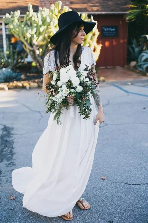 a boho bride showing off her tattoos and wearing a black hat that contrasts her dress a lot