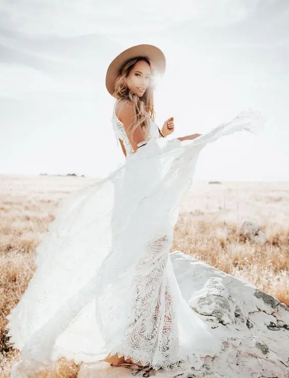 a boho bride rocking a white lace dress and a beige hat for a statement