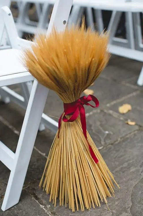 a fall wedding aisle marker of wheat with a plum-colored ribbon is ideal for a rustic wedding