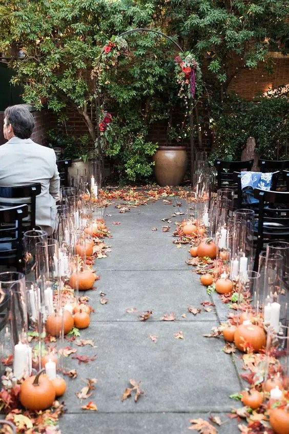 pumpkins, fall leaves and candles in tall candle holders are all that you need to embrace the season