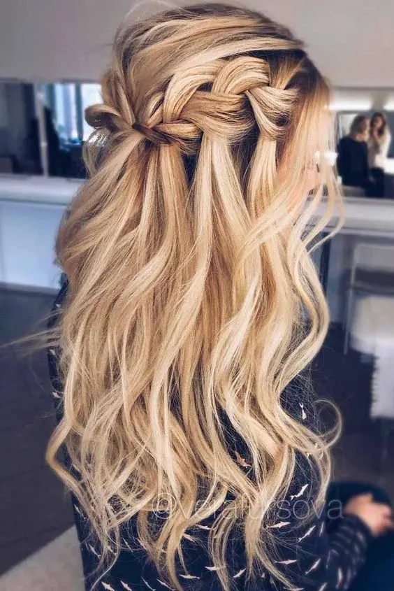 a long wavy half updo hairstyle with a braided halo and locks down for a boho feel