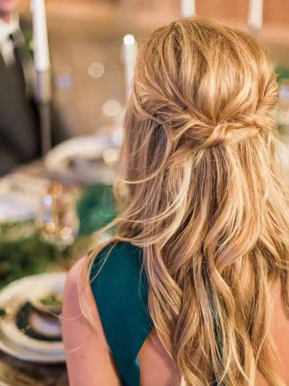 a messy twisted wavy half updo on long hair is a great relaxed idea