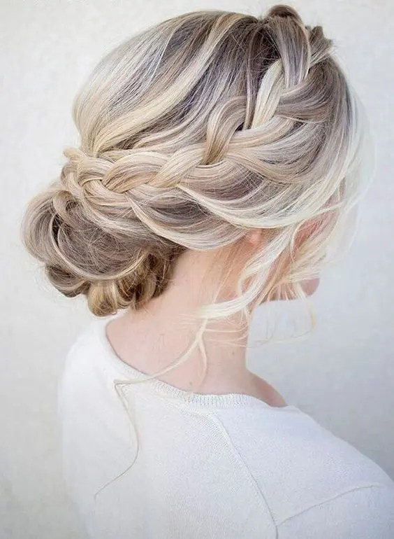 a chic braided halo with a low bun and waves down is great for a rustic or boho bridesmaid