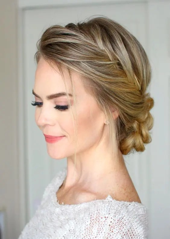 a fishtail braided halo plus a braided low bun and some hair down is a chic and comfy to wear hairstyle