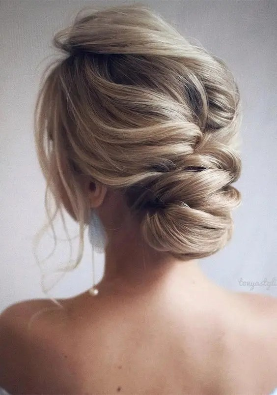a messy and voluminous low chignon with a large bump on top and locks down is gorgeous
