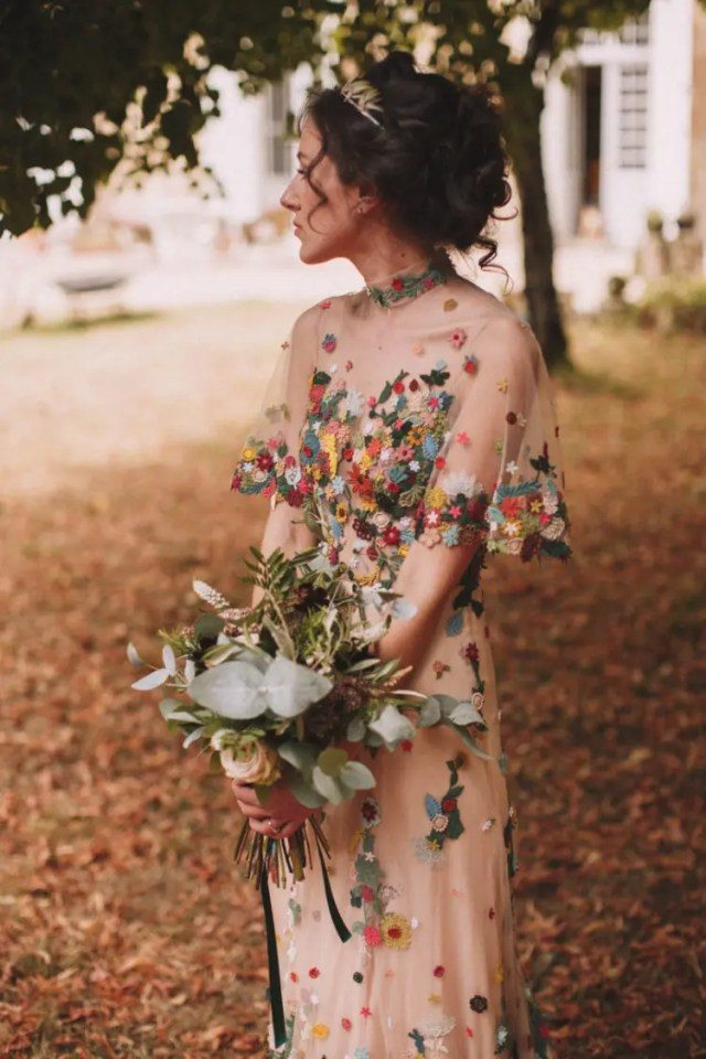 a gorgeous nude wedding dress with sheer parts and colorful crocheted floral appliques