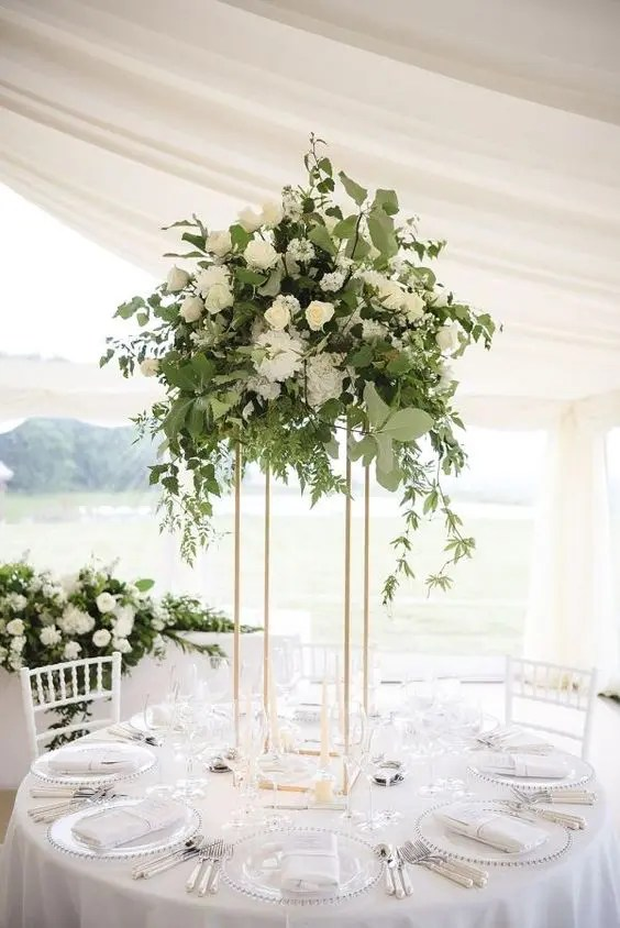 a chic eucalyptus, olive branch and white bloom centerpiece on a tall gold stand