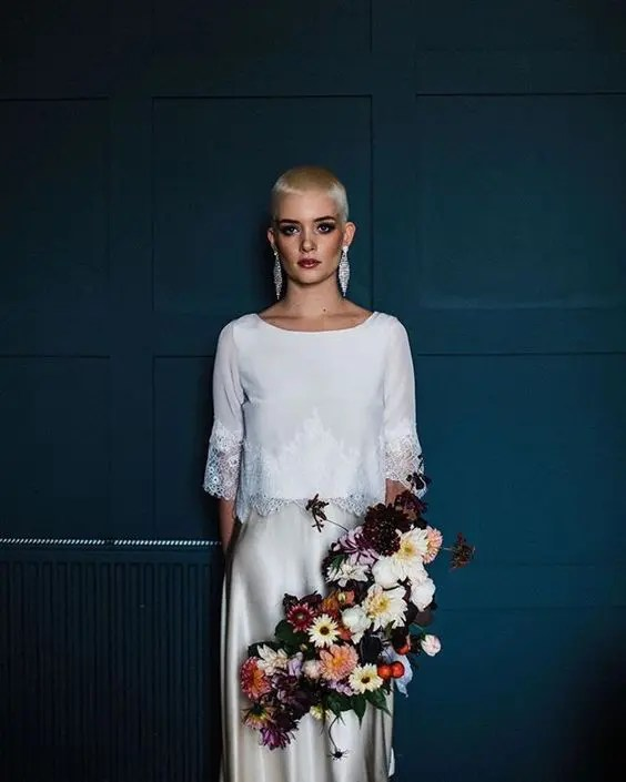 a modern bridal look with a white top with lace trim and an off-white silk skirt plus statement earrings