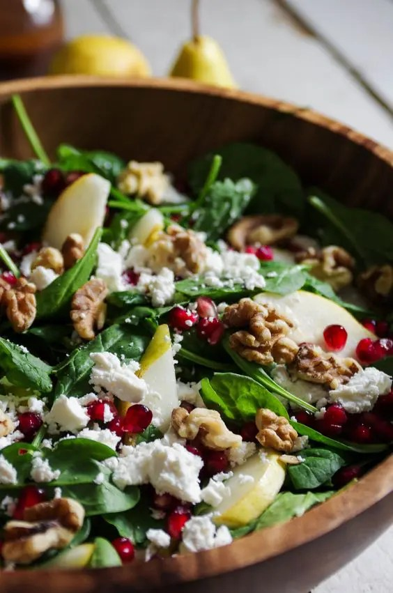 a salad with sweet pears, feta cheese, crunchy pomegranates, walnuts and spinach plus orange juice
