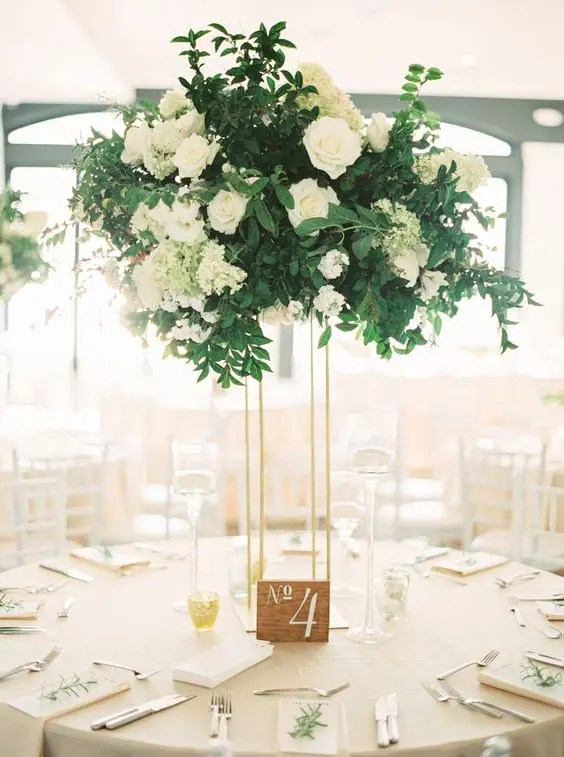 a stylish wedding centerpiece of white roses and hydrangeas and textural greenery on a tall thin stand
