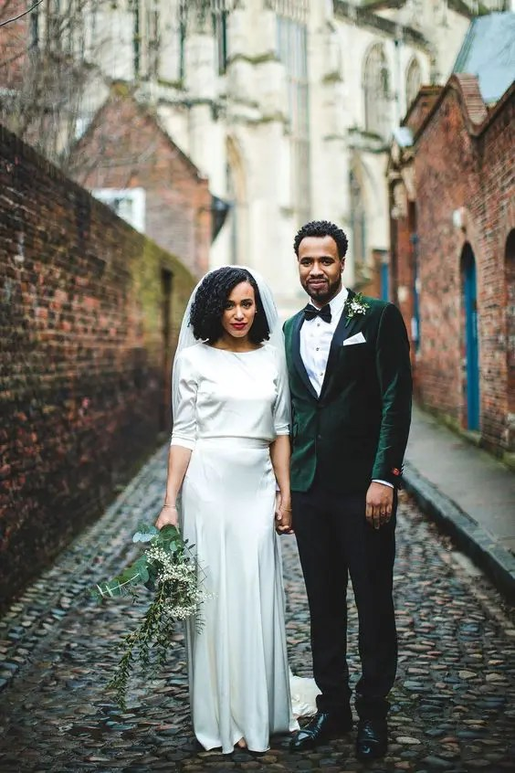 a simple and modern bridal spearate with a long sleeve top with a high neckline and a pleated maxi skirt