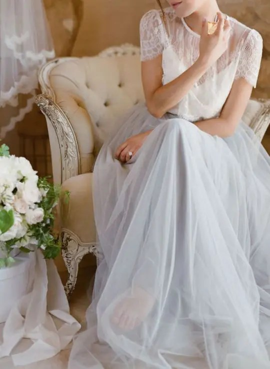 a subtle bridal look with a sheer lace top and short sleeves and a grey tulle maxi skirt