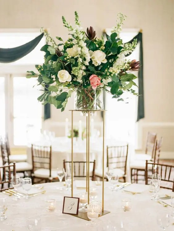 a tall and chic wedding centerpiece of white and pink blooms plus greenery on a tall gold stand