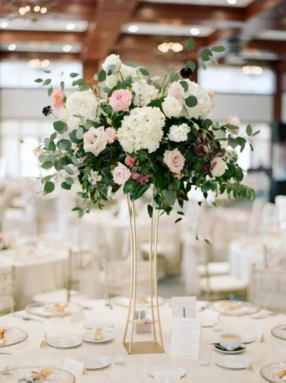 a tall hydrangea, lush greenery and rose wedding centerpiece in a gold modern vase